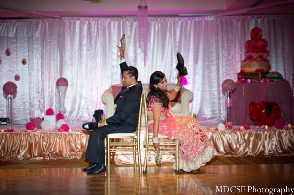 An Indian bride and groom play games at their modern pink Indian wedding reception.