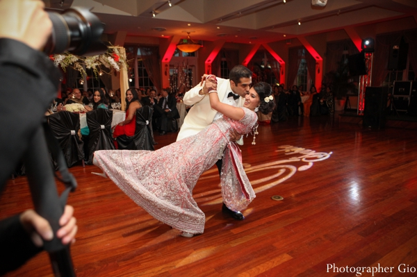 An Indian bride dances at her reception in a baby pink bridal lengha.