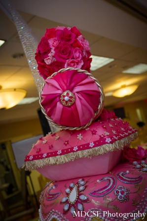 Stack of pillows for Indian wedding cake at a pink themed reception.