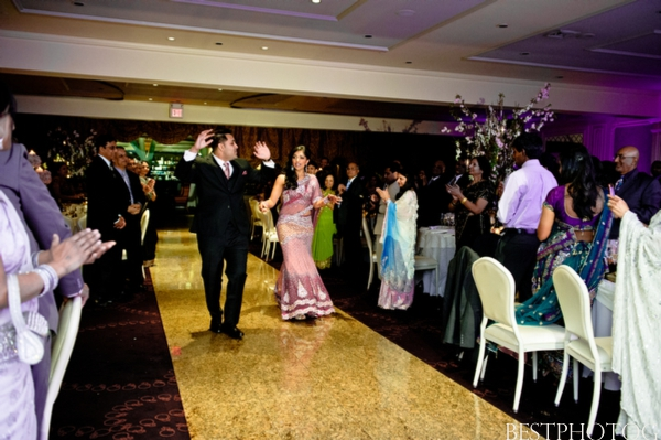 An Indian bride and groom enter a modern Indian wedding reception.