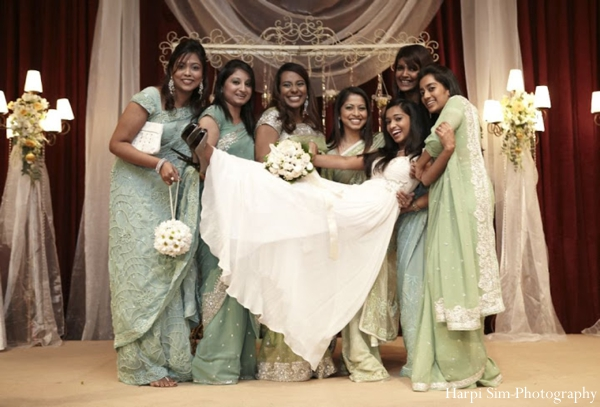 Indian bride wears white gown while indian bridesmaids wear green bridal sari fashion.
