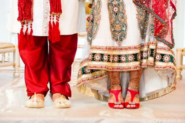 An Indian bride and groom show off their Indian wedding outfits.