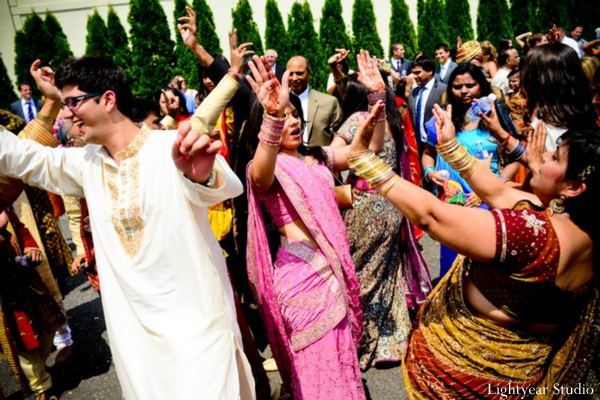 Indian wedding baraat with dancing friends and families.