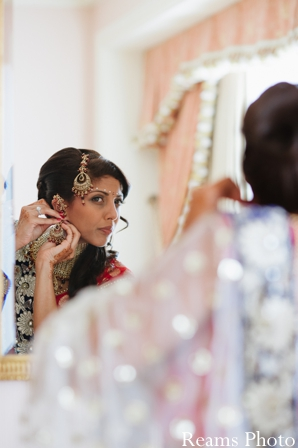 indian bride puts on indian wedding jewelry.