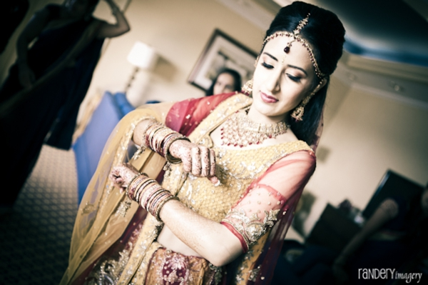 Indian bride puts on traditional indian wedding dress.