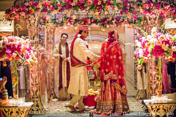 indian wedding ceremony covered in flowers at the mandap.