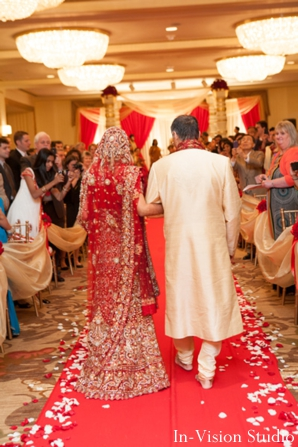 Indian bride in red wedding lengha walks to mandap