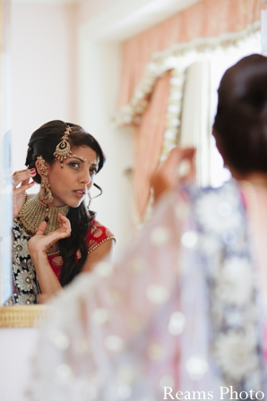 indian wedding jewelry is put on by indian bride.