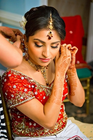 Indian bride wears red bridal lengha at indian wedding.