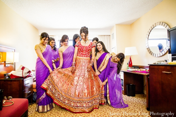 indian bride puts on red wedding lengha with bridesmaids in purple saris.