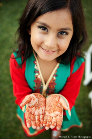 Mehndi on hands of pakistani wedding flower girl.