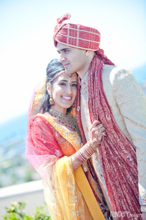 Indian bride wears red and yellow wedding lengha next to her groom.