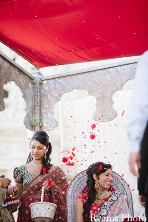 Indian bride has petals thrown at her in indian wedding tradition.