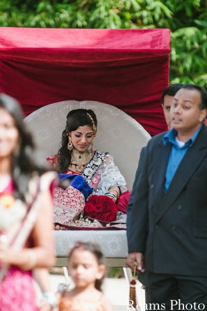 Indian bride rides in palanquin to indian wedding ceremony.