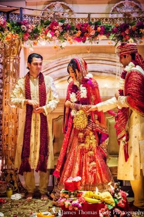 indian wedding bride and groom under mandap.