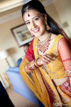 Indian bride wears yellow and red bridal lengha.
