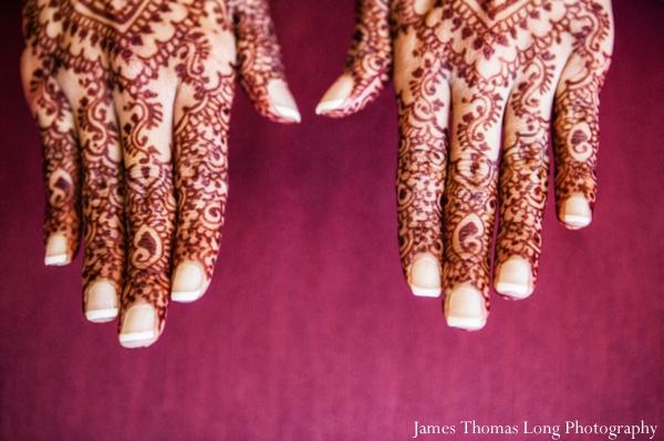 indian bride wears mehndi on hands.