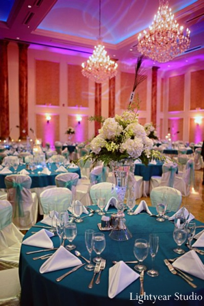 Teal blue and purple table setting at indian wedding reception.