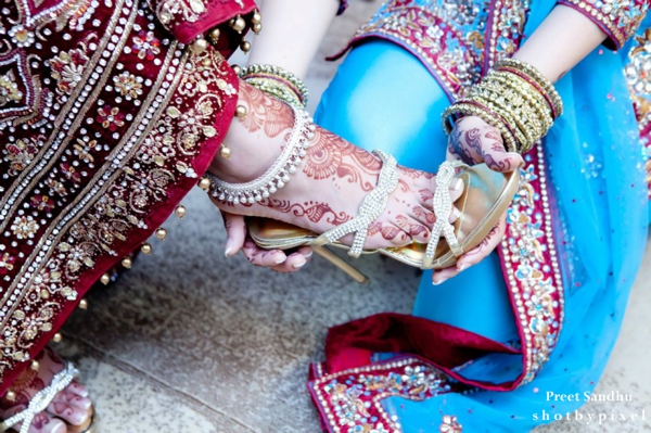 Indian bride puts on indian bridal heels.