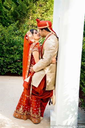 Indian bride and groom kiss in indian wedding portrait.