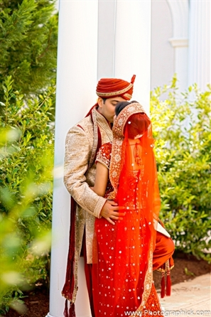 Indian bride and groom share a kiss on their indian wedding day.
