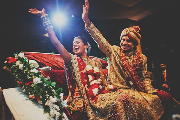 An Indian bride and groom wave goodbye to family at Indian wedding ceremony.