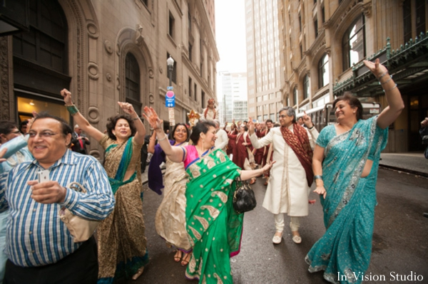 Indian wedding party goers dance at baraat.