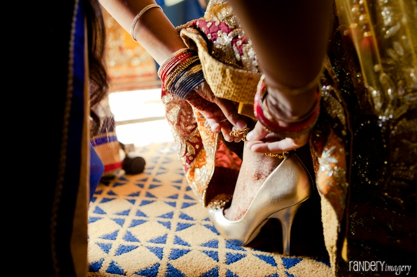 Indian bride slips on gold bridal shoes to match wedding lengha.