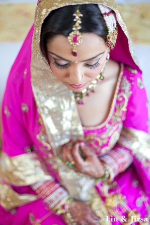indian bride wears pink bridal outfit to sikh wedding ceremony.
