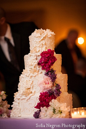 Indian wedding cake with fresh flowers in pink and purple.