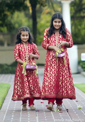pakistani wedding flower girls in matching red outfits.