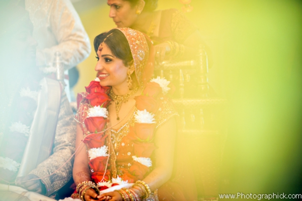 Indian bride wears traditional bridal lengha with jaimala flower garland.