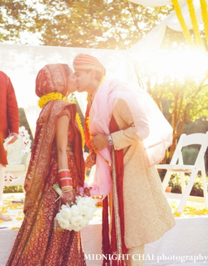 indian bride and groom kiss at indian wedding ceremony