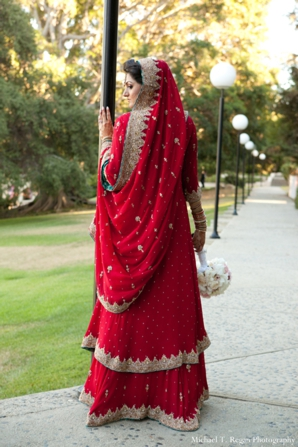 Pakistani bride in red lengha with gold trim.