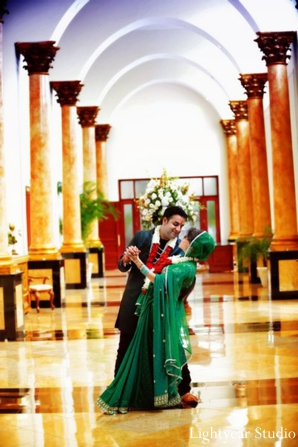 Indian bride wears modern green bridal sari fashion.
