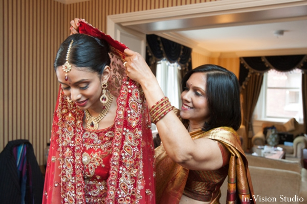 indian bride puts on indian wedding gown in red
