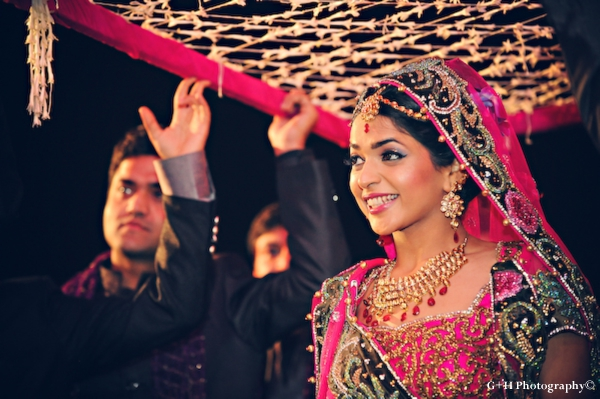 Indian bride enters indian wedding ceremony in hot pink wedding lengha