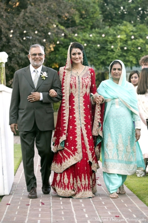 Pakistani bride in red lengha with gold and green detailing.