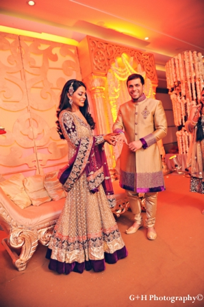 Indian bride wears gold and purple wedding outfit for engagement party