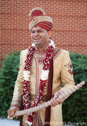 Indian groom poses in traditional Indian wedding outfit.