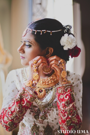 Indian bride puts on indian bridal jewelry.