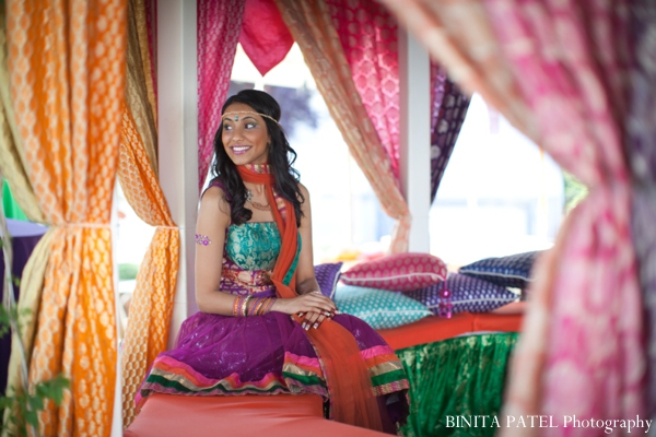 Indian bride smiles at her bridal mehndi party.