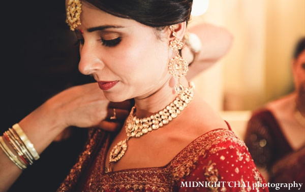 Indian bride puts on indian bridal jewelry set.