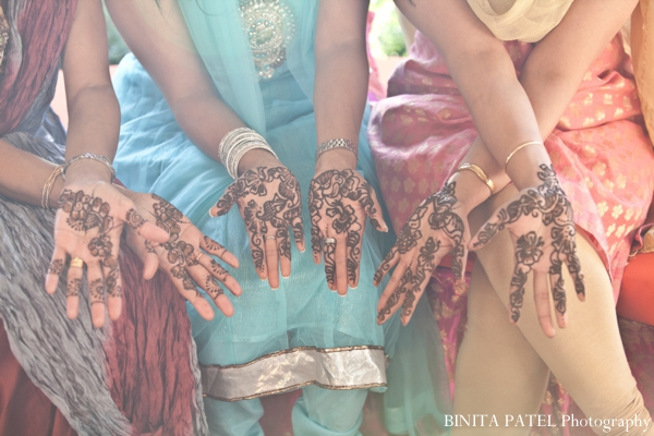 Henna artist draws bridal mehndi for Indian bride and bridesmaids.