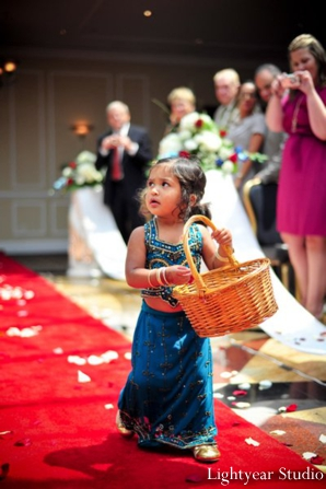Indian wedding flower girl walks the aisle.
