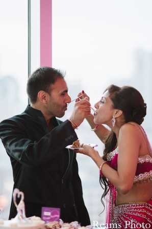 indian bride and groom eat indian wedding cake.