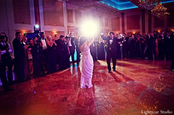 Indian bride and groom dance at modern indian wedding reception.