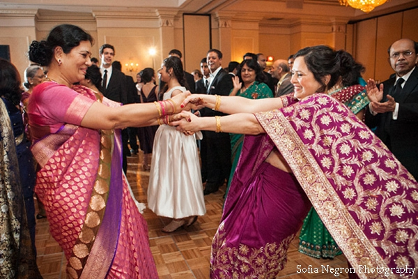 Indian wedding reception with guests dancing in wedding saris.