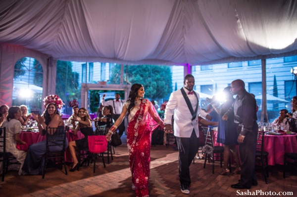 Indian bride and groom enter fusion indian wedding reception.