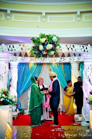 Indian bride and groom under a white mandap.